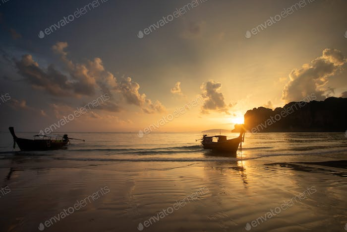 Amazing sunset with longtail boats silhouette at Railay beach, T