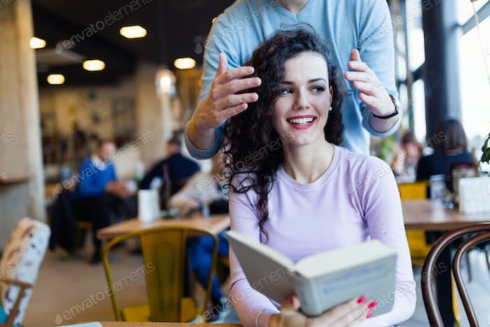 Young couple reading books in coffee shop