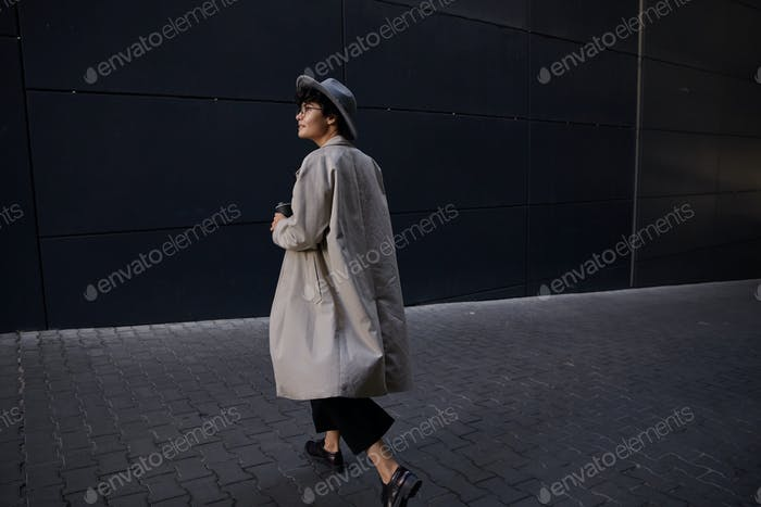 Fashionable young pretty curly woman with short haircut walking on city street in beige long trench