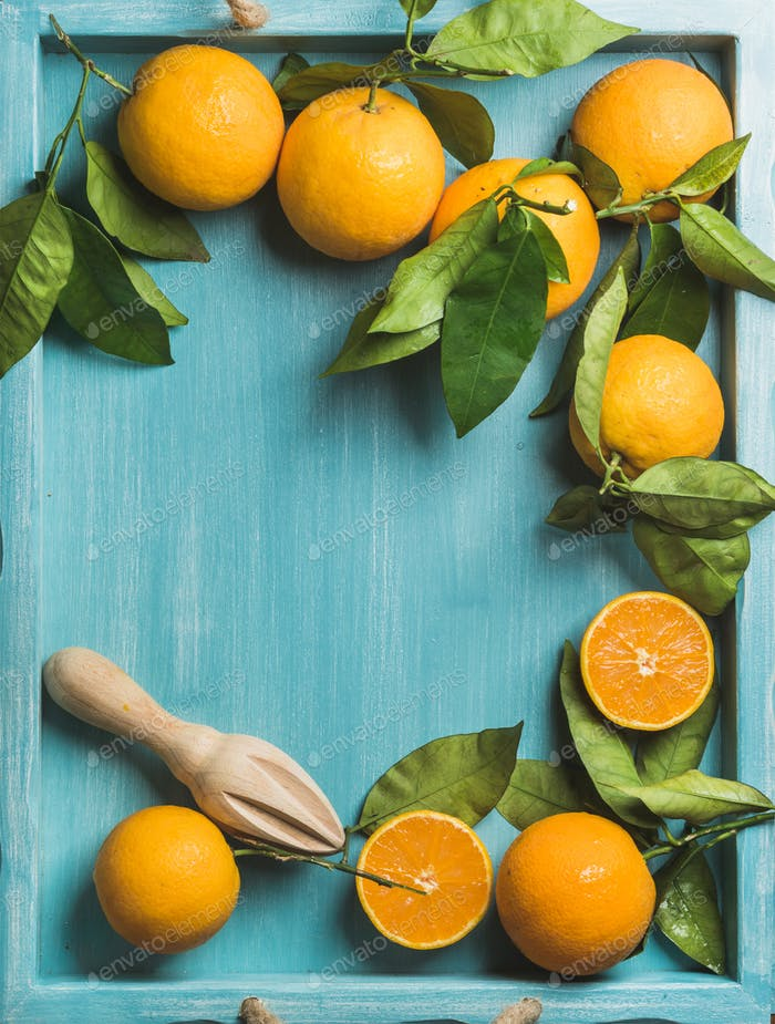 Fresh oranges with leaves on blue painted wooden background, copy space