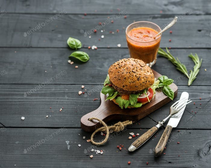 Fresh homemade burger on dark serving board with spicy tomato sauce, sea salt and herbs