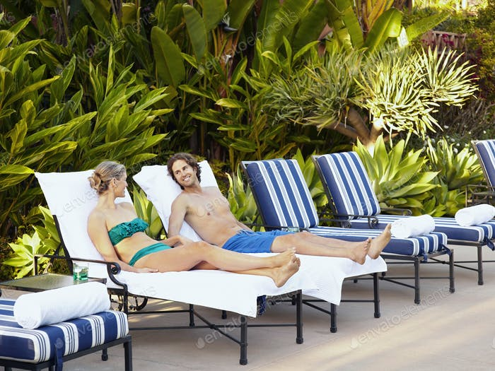 Caucasian couple laying in lounge chairs at poolside