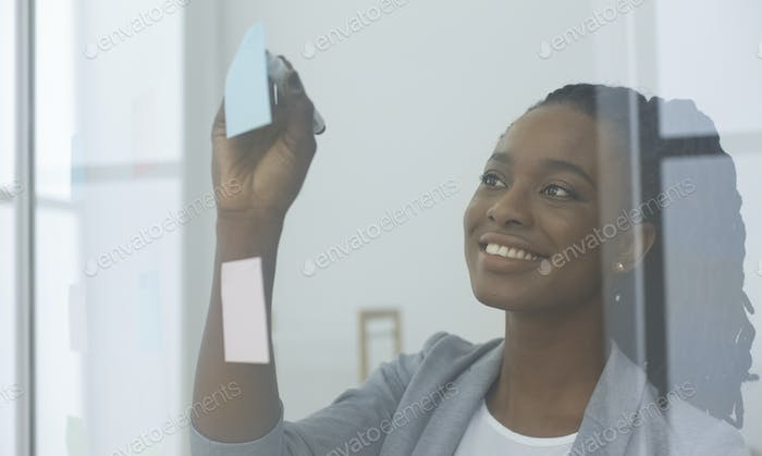 Businesswoman Reading Colorful Notes On Glass Board In Office