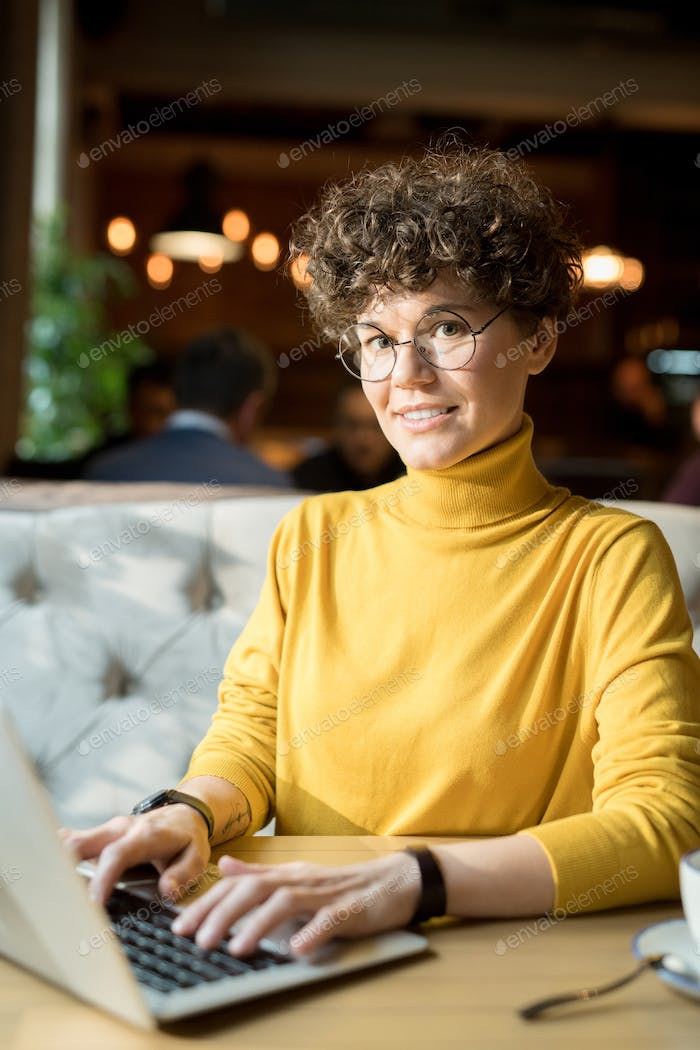 Cheerful hipster woman working with laptop