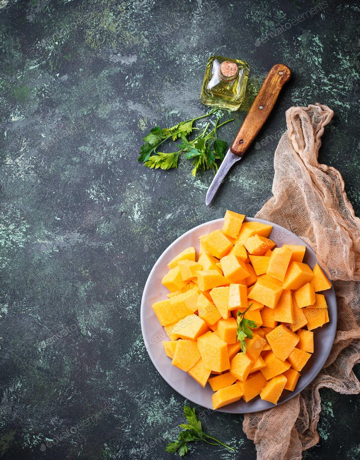 Raw chopped pumpkin on concrete background