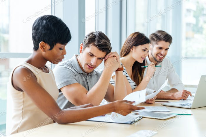 Business people sitting and working with documents in office