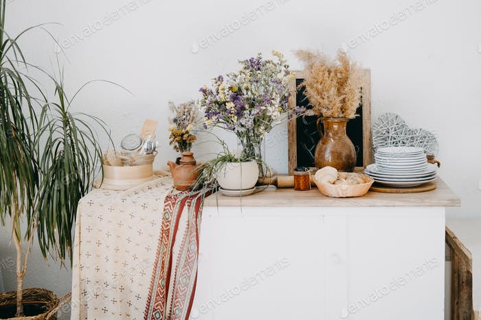 Home kitchen rustic interior decor of apartment with table, clay and wooden utensil, flowers, home