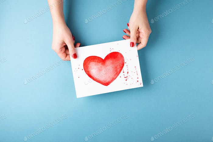 Female`s Hand Holding Card with a Painted Heart.
