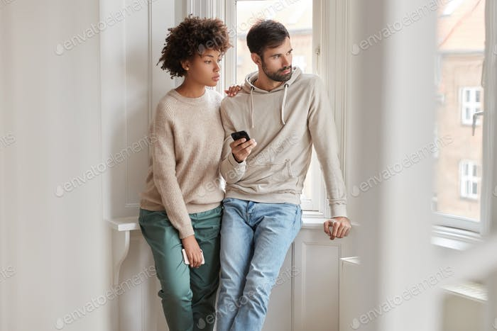 Horizontal shot of thoughtful hipster couple, read news in morning from cellular, stand in empty apa