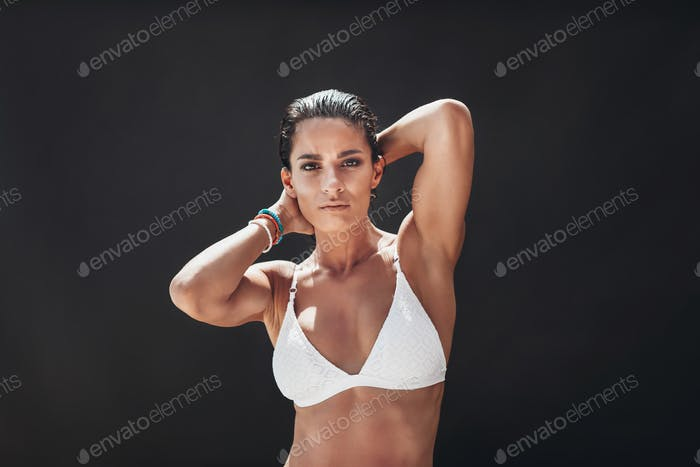 Woman in white bikini posing on black background