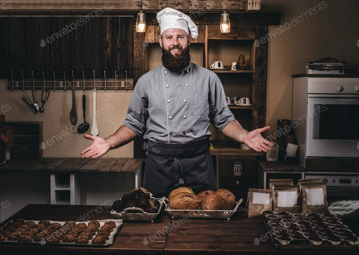 Promotion in bakery. Handsome bearded chef in uniform showing fresh bread in the kitchen