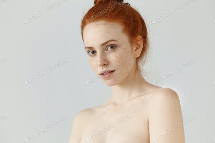People, youth, beauty and skin care concept. Portrait of beautiful young redhead woman posing toples
