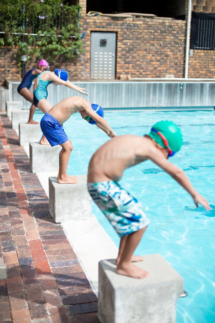 Swimmers taking position to jump in swimming pool