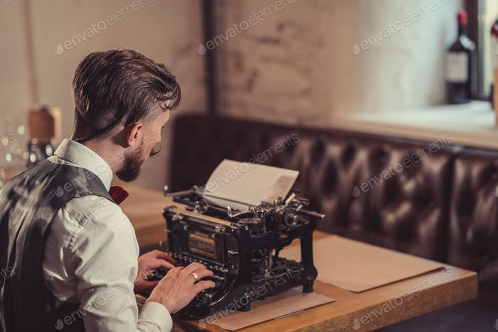 Arbeitender Mann, der auf einer Retro-Schreibmaschine tippt