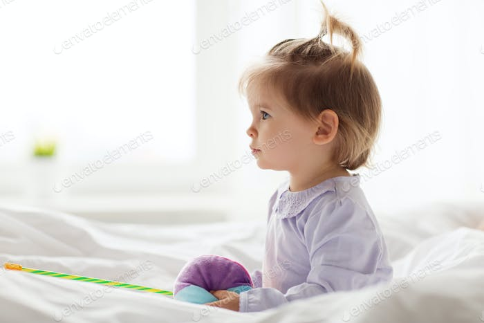 lovely little girl with toys in bed at home