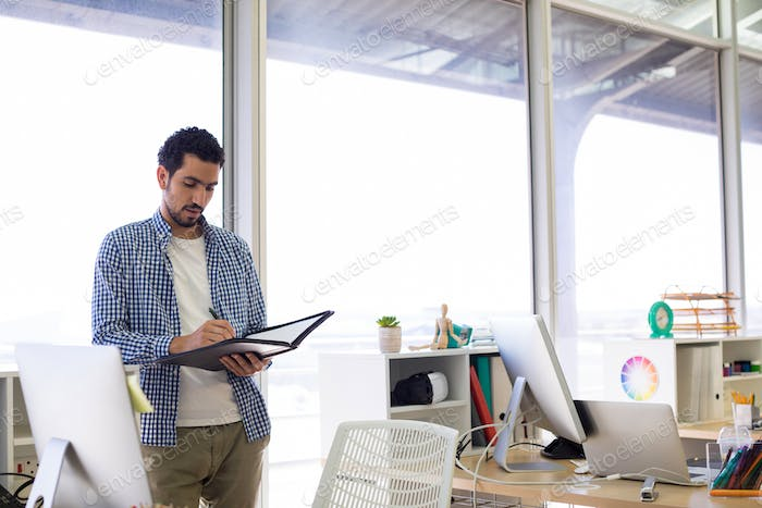 Male executive writing in diary at his desk