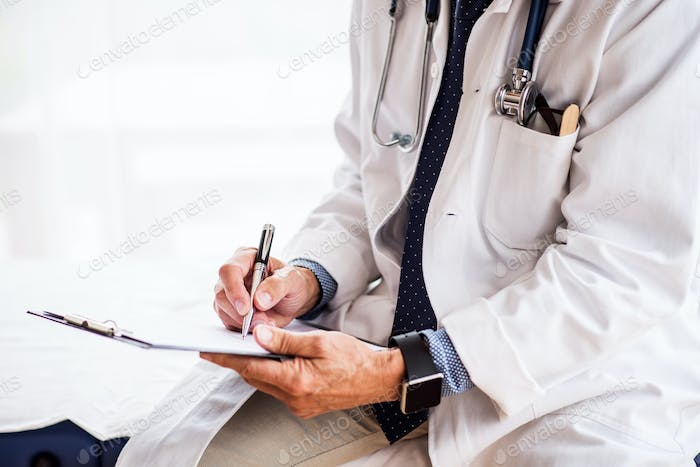 Senior doctor with smartwatch in office.