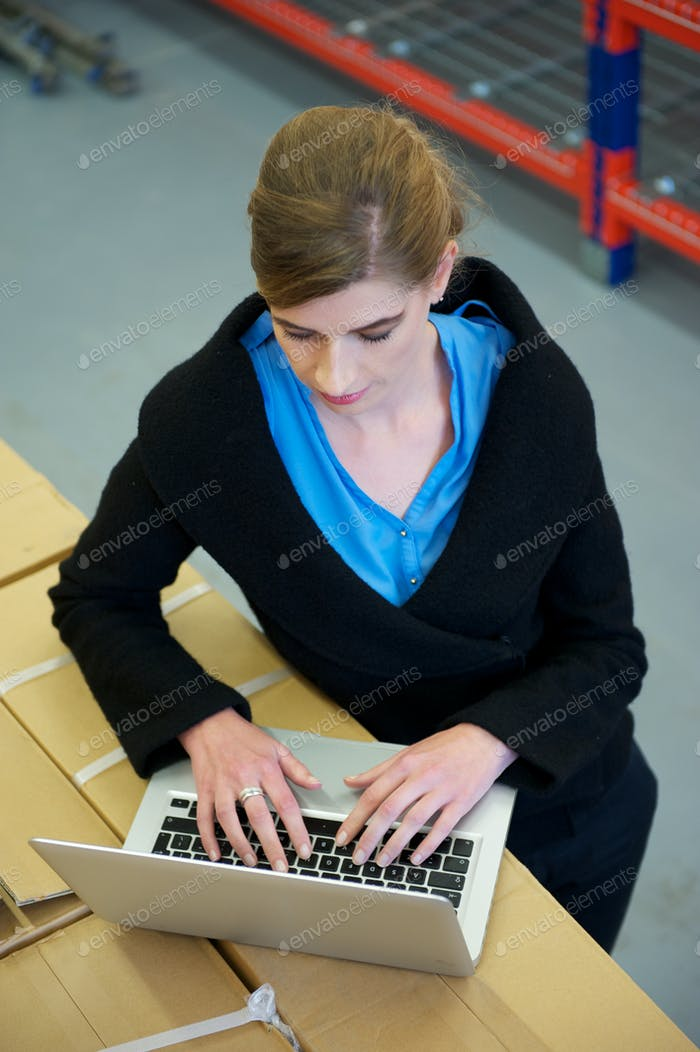 Businesswoman typing on laptop computer in warehouse