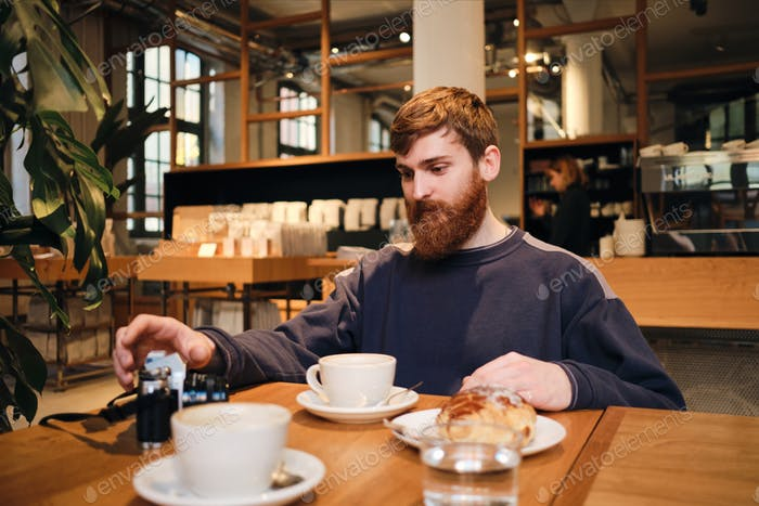Young handsome bearded man having coffee break in cafe