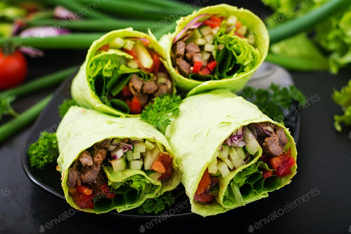 Shawarma from juicy beef, lettuce, tomatoes, cucumbers, paprika and onion in pita