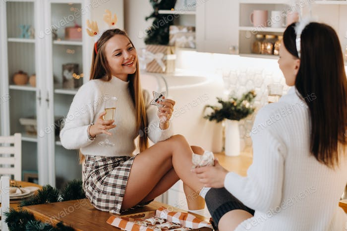 two girls in a cozy home environment in the kitchen with champagne in their hands for Christmas