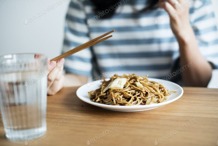 Asian woman eating noodles