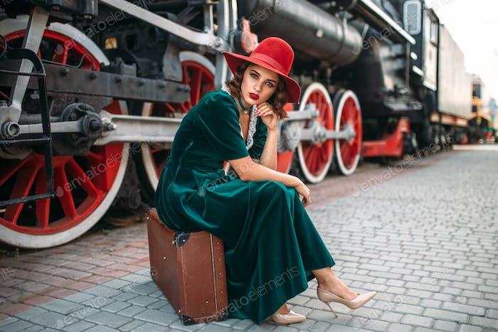 Frau sitzt auf Koffer gegen Dampfzug