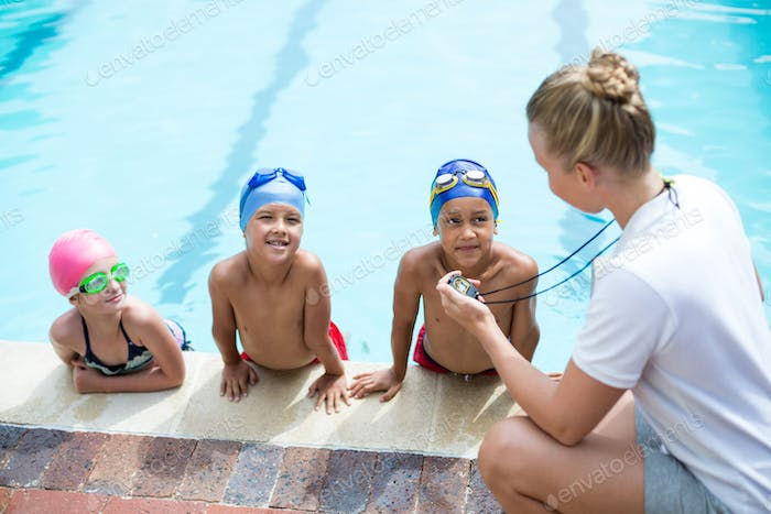 High angle view of female swimming trainer teaching students