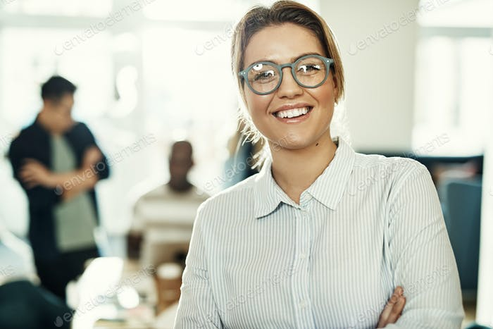 Smiling businesswoman in an office with colleagues in the background