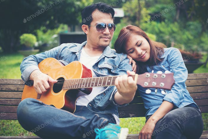 Young couple in love playing acoustic guitar in the park while sitting on the bench together.