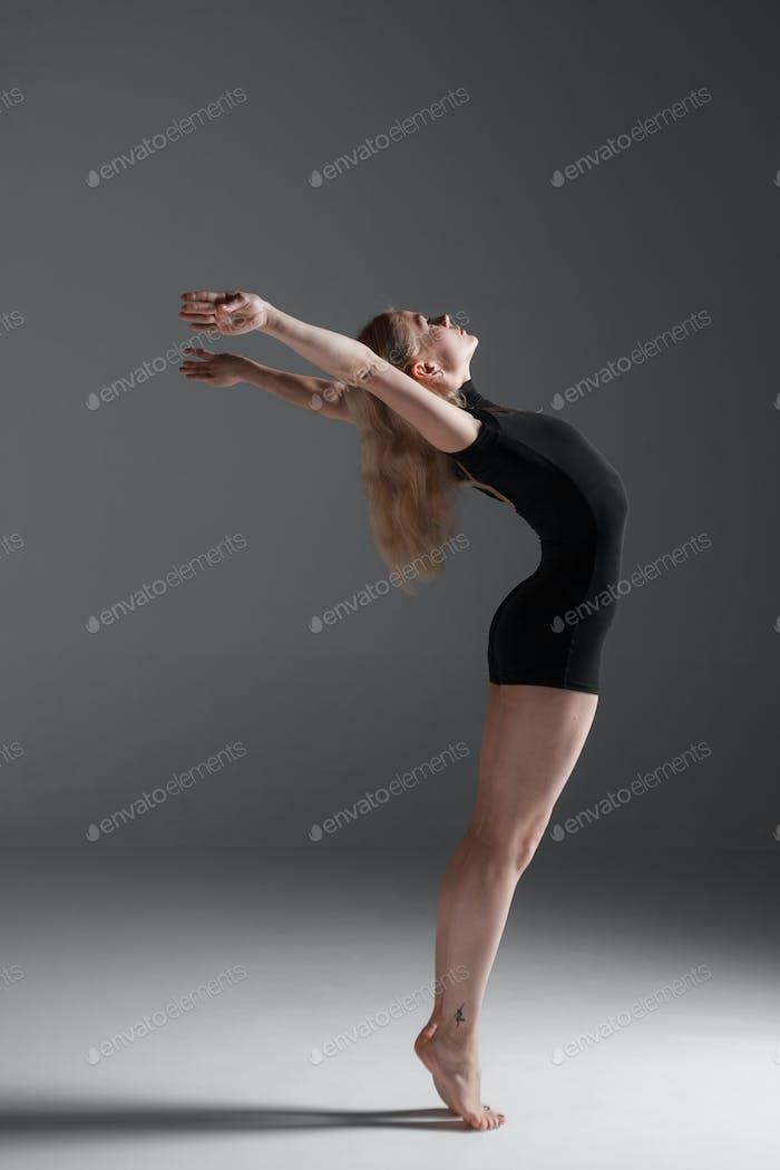 Junge schöne moderne Stil Tänzerin posiert auf einem Studio-Hintergrund