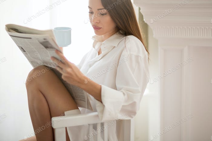 Woman reading news during breakfast