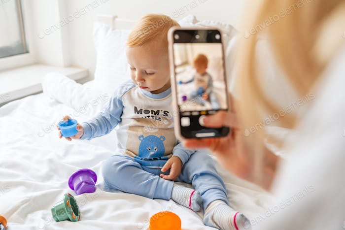 Mother taking photo of her blonde baby son on mobile phone