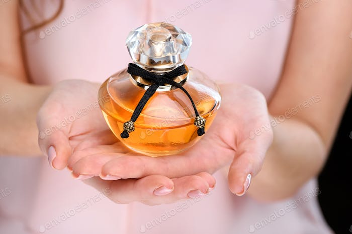 cropped shot of woman holding bottle of perfume