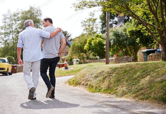 Rear View Of Senior Father With Adult Son Talking As They Walk Along Country Road Together
