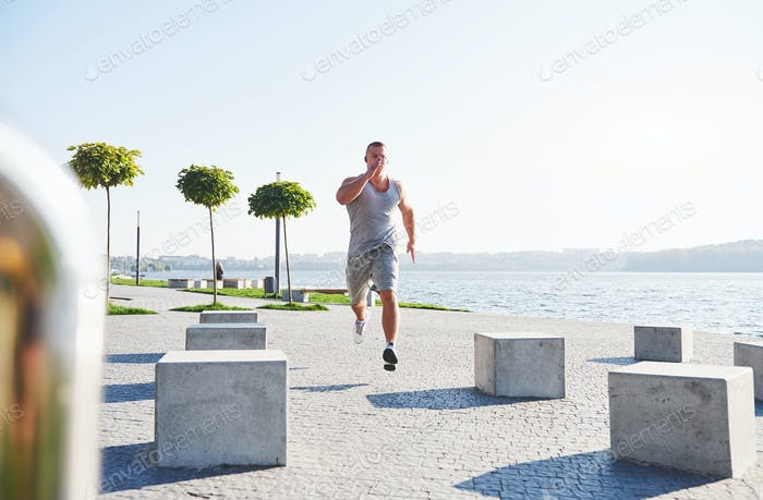 man runner doing stretching exercise, preparing for morning workout in the park