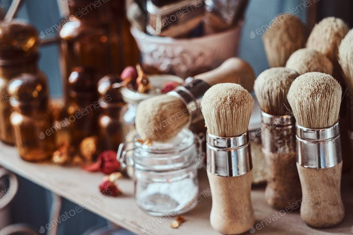 Glass jars, different brushes and other tools on a shelf at art studio