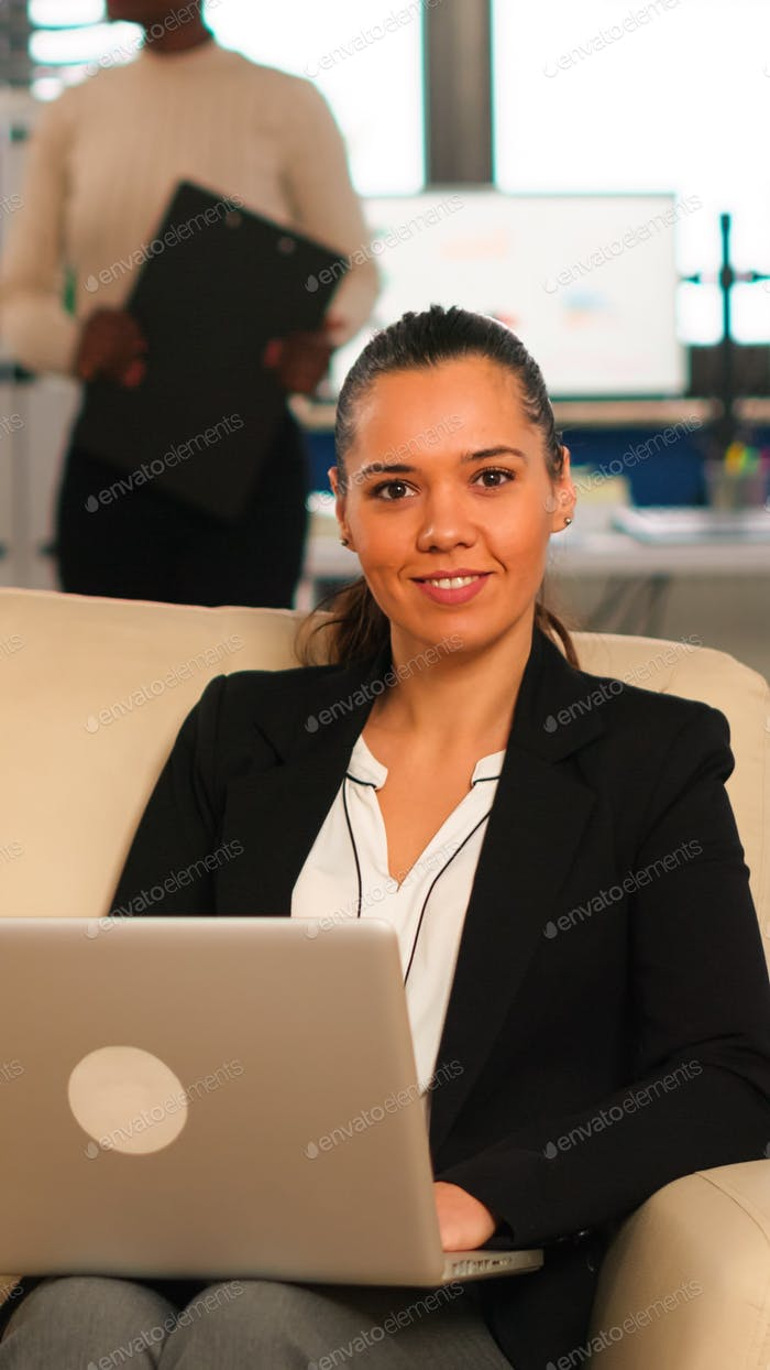Hispanic business woman smiling at camera sitting on couch typing on computer