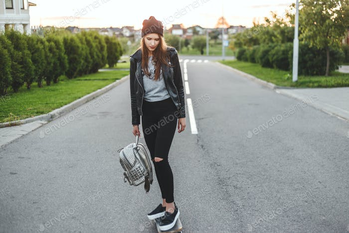 Beautiful and fashion young woman ride on a skateboard