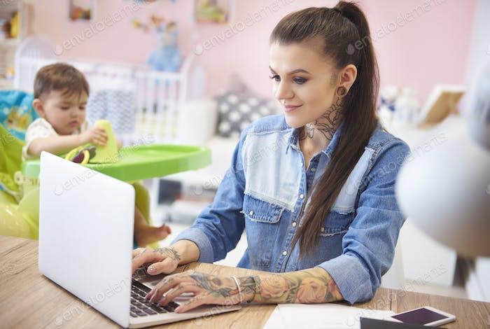 Mama arbeitet am Laptop und verspielter Sohn neben