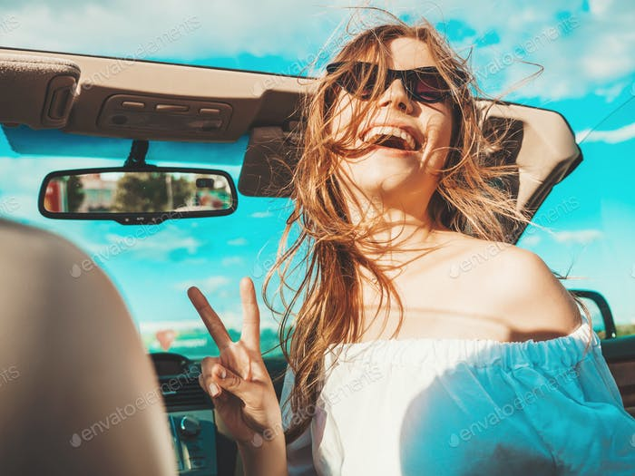 Portrait of young funny woman in cabriolet car