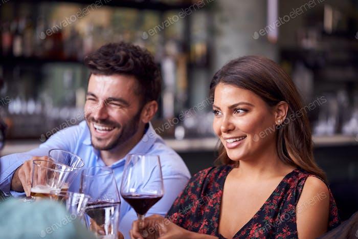 Reunión de grupo de amigos en restaurante celebrando y haciendo un brindis