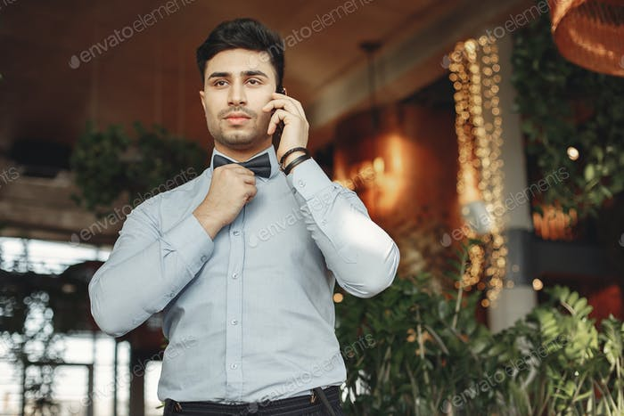 Stylish businessman in a blue shirt standing indoor