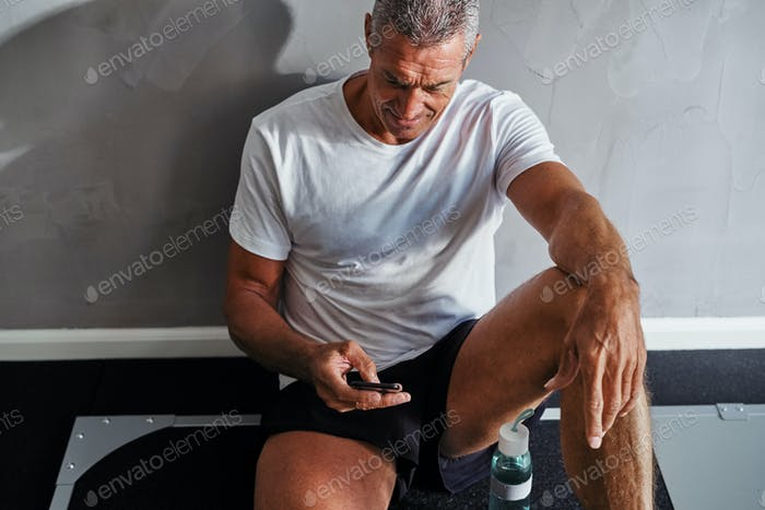 Mature man checking his cellphone after a work out