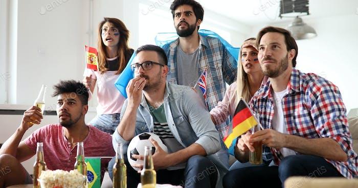 Menschen, Freizeit, Rivalität und Sportkonzept. Glückliche und traurige Freunde oder Fans beobachten Spiel zu Hause