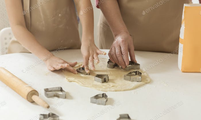 Home baking. Child and granny cutting cookies out of raw dough at table, closeup