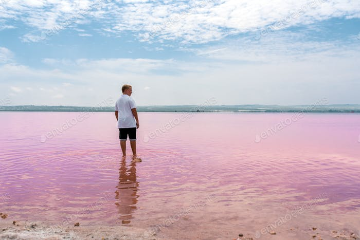 Side view of cute teenager boy wearing summer clothes on pink lake
