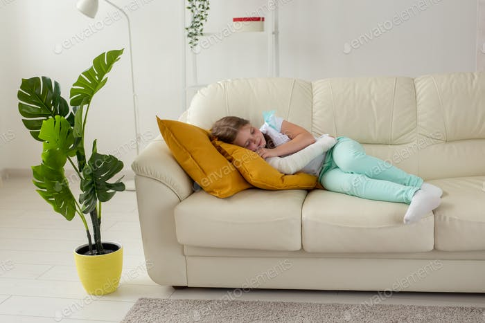 Child with a cast on a broken wrist or arm lying on a couch. Recovery and kid concept