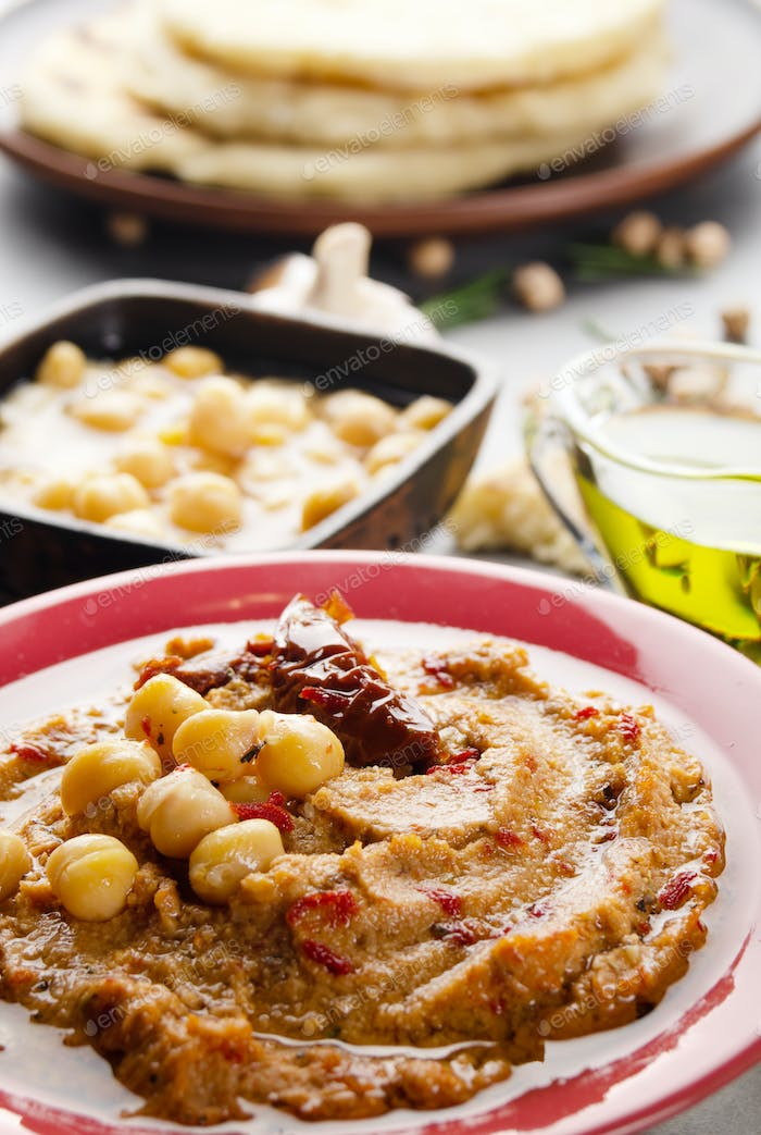 Fresh homemade Hummus in clay dish topped with olive oil, chickpeas, spices and sun dried tomatoes