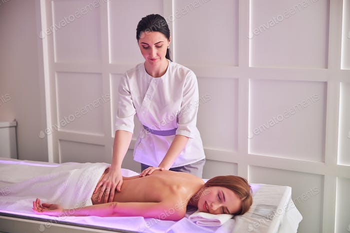 Elegant pretty woman with perfect body relaxing at the spa complex procedure in massage cabinet
